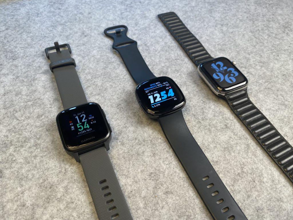 Garmins Venu SQ neben einer Fitbit Sense und einer Apple Watch